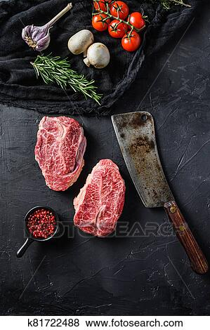 Raw top blade cut organic meat with vegetable rosemary and other ingredients for bbq or gtrill top view over black stone background vertical Stock ...
