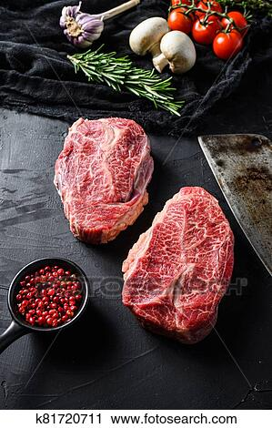 Raw top blade cut organic meat ner butcher meat clever knife for bbq or gtrill top view over black stone background close up vertical selective ...