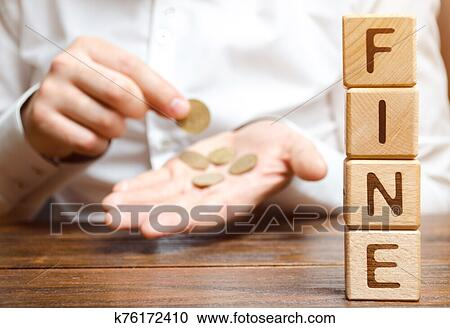 Wooden blocks with the word Fine and a man who calculates the size of the fine. Monetary penalty imposed in the form of punishment. Committing ...