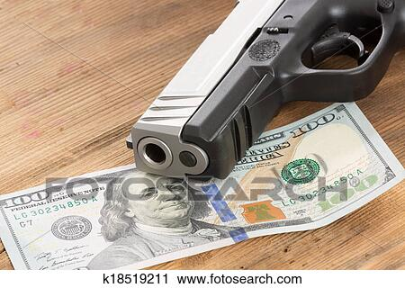 Muzzle of a gun with a 100 dollar bill Stock Image | k18519211 | Fotosearch