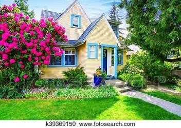Pequeño casa amarilla exterior con florecer rododendro Colección de imágen k39369150 Fotosearch