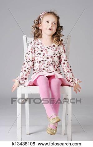 little girl chairs ergonomic chair laptop stock image of cute sitting on the white posing beautiful smiling making faces