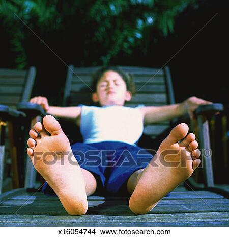 Close-up of the feet of a boy (6-8) reclining on a lawn chair Picture | x16054744 | Fotosearch