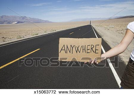 Stock Photo of Hitchhiker with sign to anywhere on empty