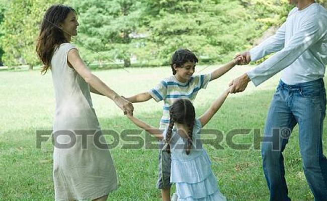 Family Outdoors On Lawn Playing Ring Around The Rosy Stock