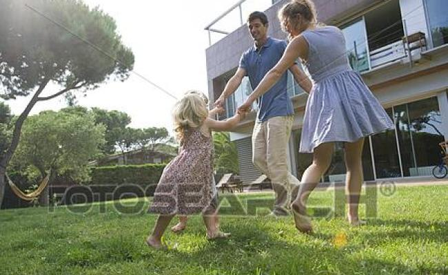 Family Playing Ring Around The Rosy Outdoors Stock Photo