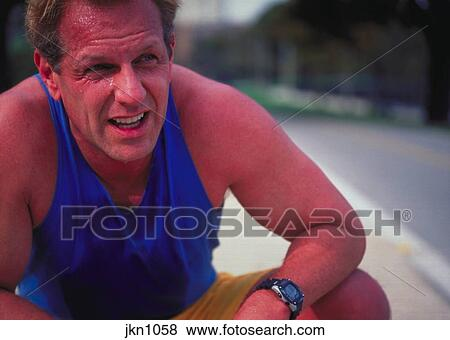 An out of breath jogger bending on his knees by the side of the road as sweat drips from his forehead. Stock Photo | jkn1058 | Fotosearch