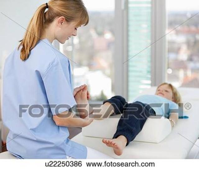 Doctor Examining Boys Feet In Office