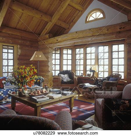 Stock Photograph of LIVING ROOM  Log house Native American rugs Wicker furniture Pine tables