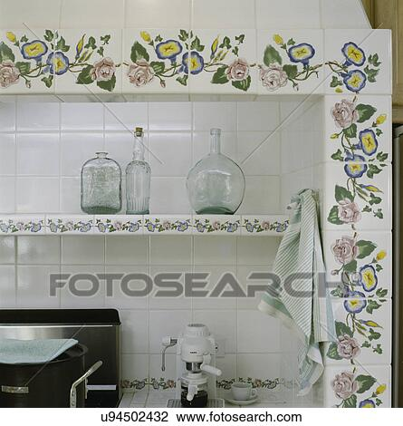 Stock Photo of Detail of shelf in alcove stove area tile back splash and decorative painted