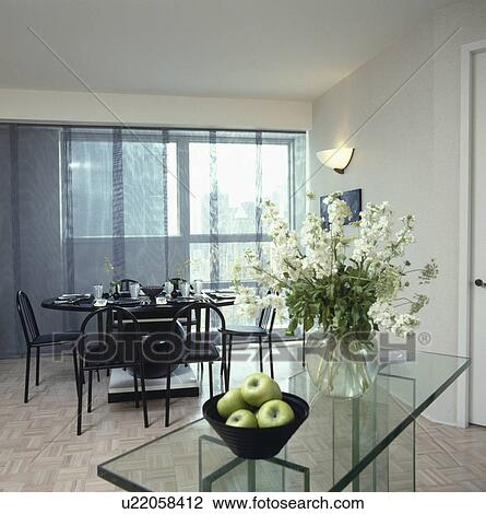 stock photo white stocks in glass vase on glass side table in modern white