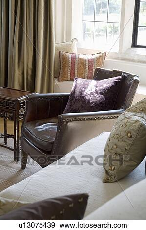 green cushions living room wood tiles design stock photograph of old leather armchair beside cream sofa with in country