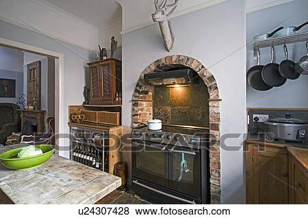 Pictures of Range oven in fireplace alcove with brick arch in traditional kitchen u24307428