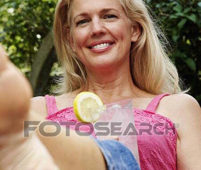 Portrait Of A Mature Woman Holding A Glass Of Lemonade And Smiling