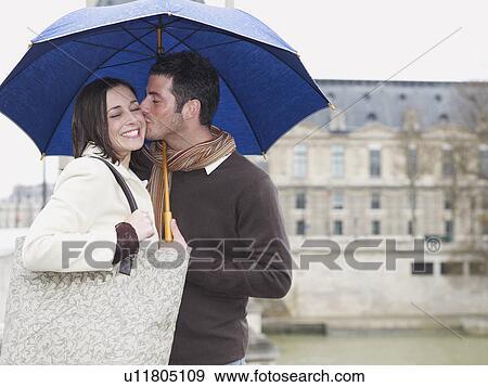 Stock Fotograf  mann kssen frau unter umbrella