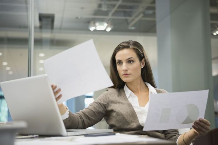 Businesswoman analyzing documents in office