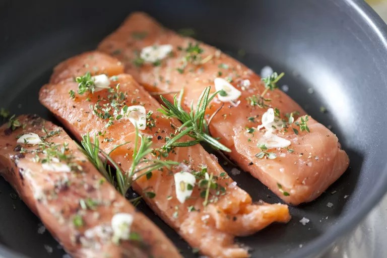 Filete de salmón en una sartén con ajo y hierbas