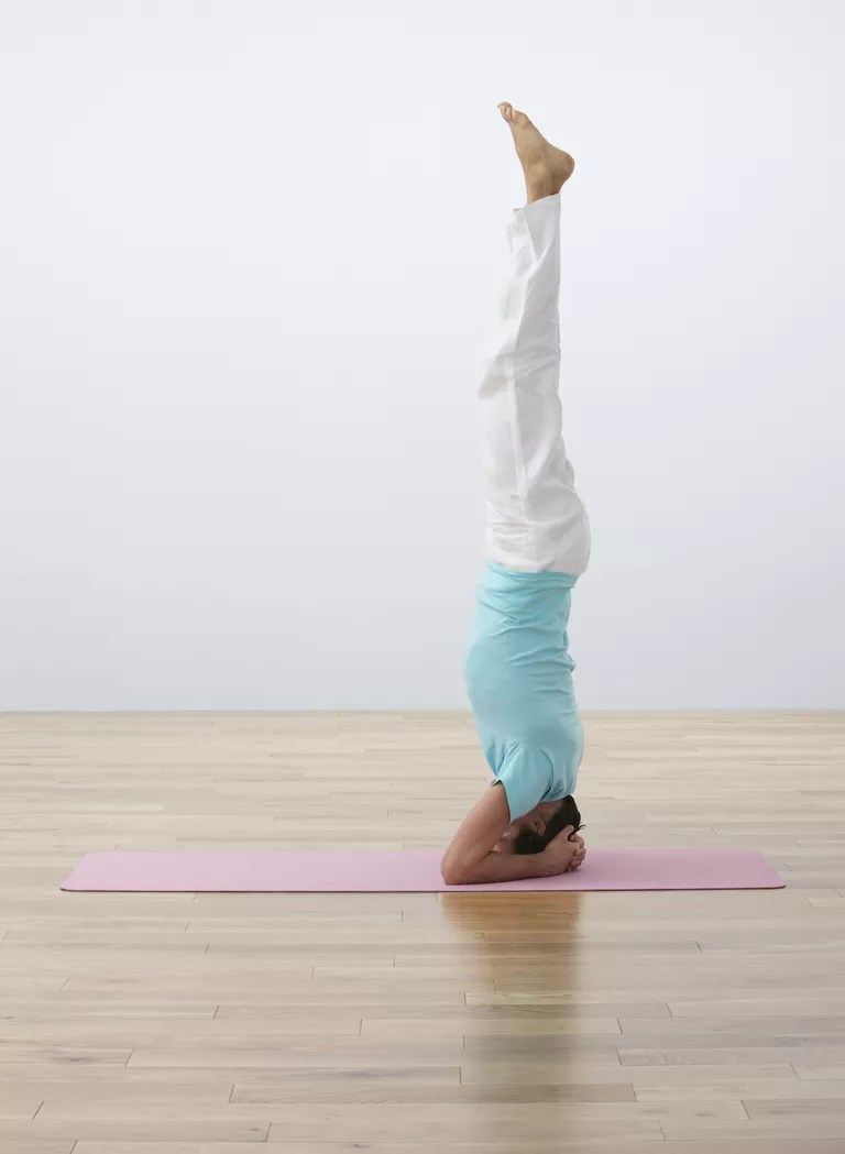 Man performing headstand on exercise mat, side view