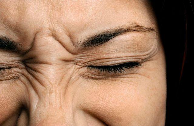 Cerca de la cara de una mujer, arrugado de dolor.