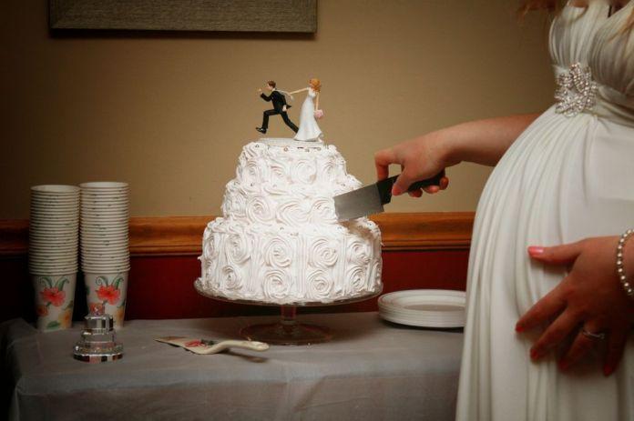 Pregnant woman cutting her wedding cake