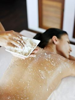 A woman receives an exfoliating scrub.
