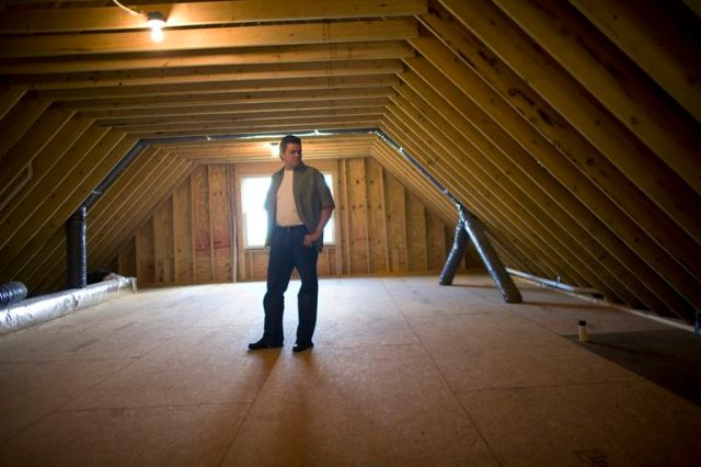 man standing in empty attic