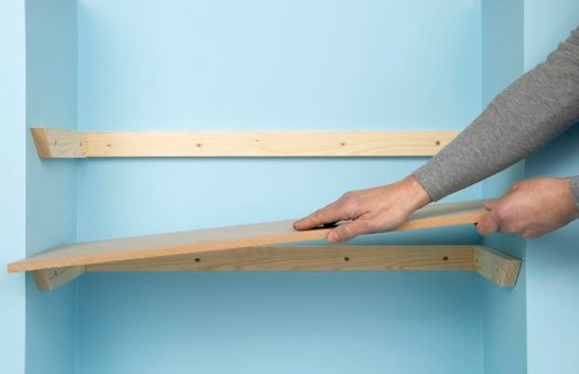 Man Installing Wooden Shelf On Battens Attached To Blue Wall