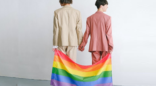 LGBTQ+ couple in suits holding Gay Pride flag