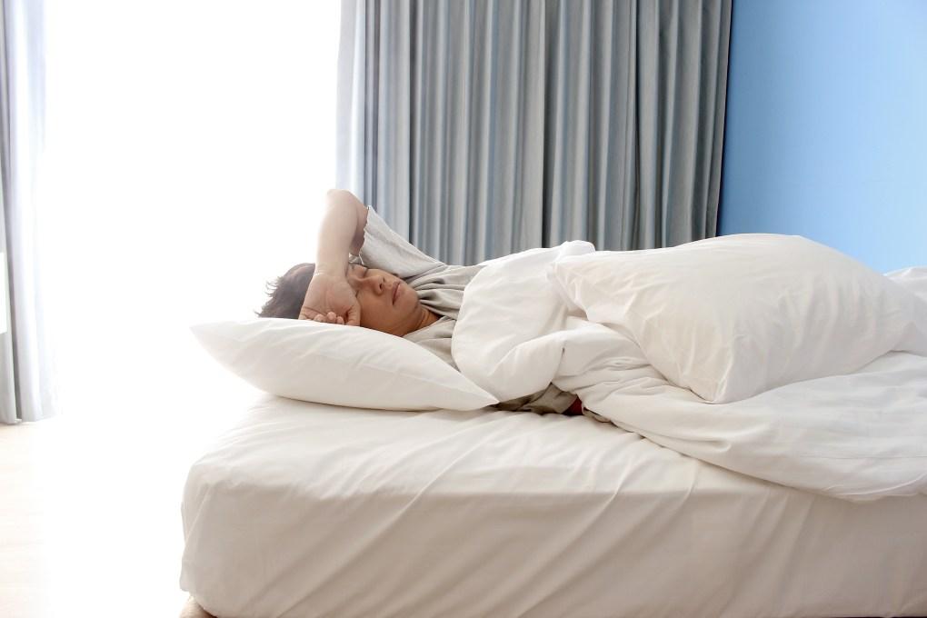 man sleeping on bed in hotel bedroom