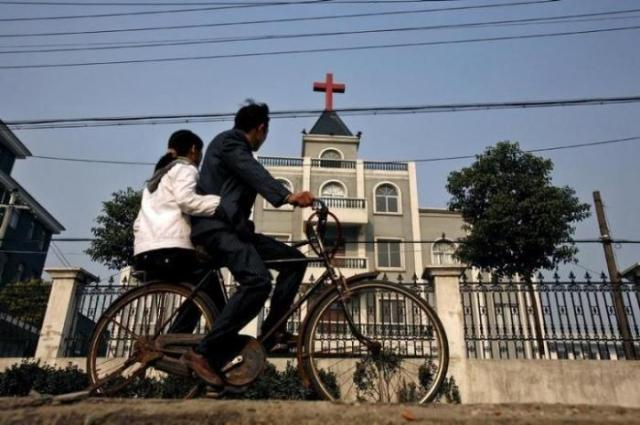 A local resident rides a bicycle past a church in Xiaoshan