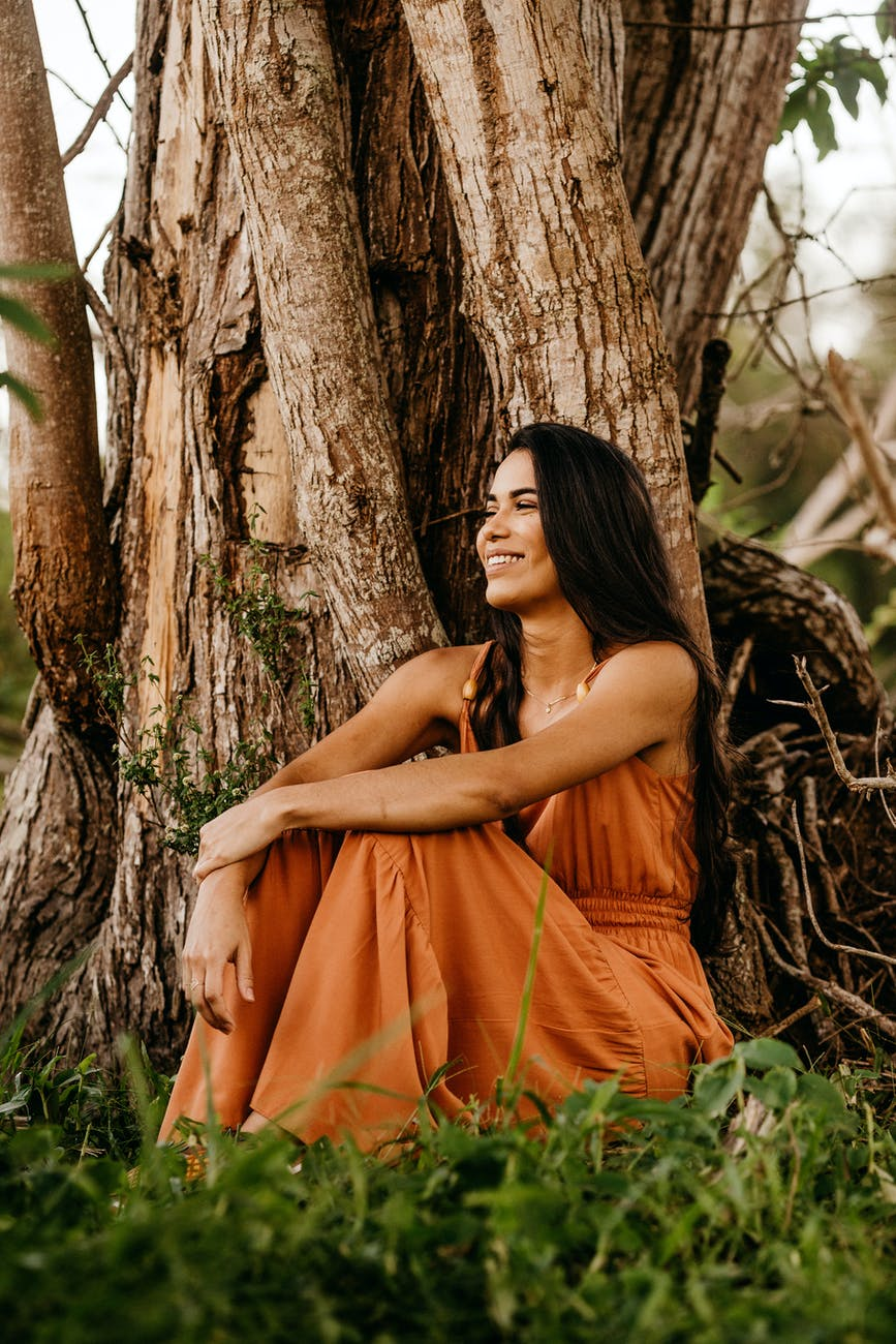 joyful woman in stylish maxi dress resting near old tree