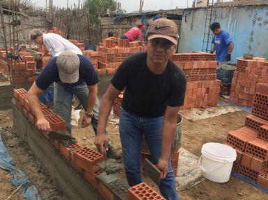 Millard Zenon laying bricks on 101st house in La Florida.