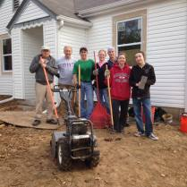 Photo: Tara and her family and friends and Fuller Center Volunteers pose for a photo in front of the Olive Street House
