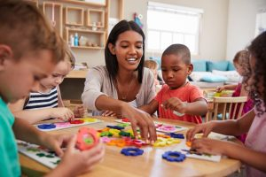 Latinyx woman, young, medium complexion, shoulder length dark hair, playing with five multi-racial children