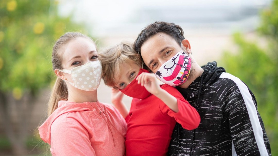 green trees and blue sky in blur background, white woman, long blond hair, mav blouse, wearing a white mask, white boy, boy haircut blond hair, red shirt, red mask, being held by white woman and white man, white man, short dark hair blk and white shirt wearing a white, pink, black mask