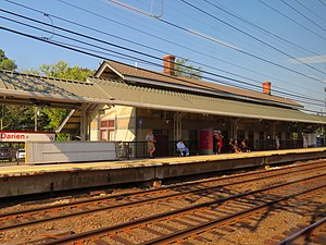 train station, brown in color, green shade roof, two chimneys. two sets or railroad tracks, wires overhead