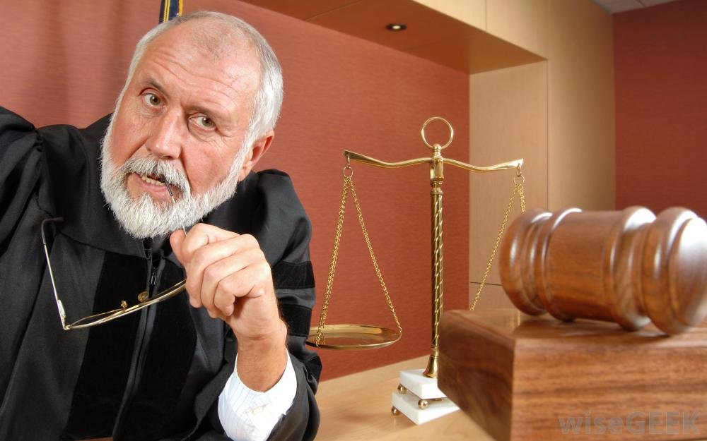 White male with grey beard black robe glass tip in mouth gavel in front ot him scales of justice in front of him