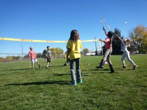 three white girls, about ten years, playing badminton on green grass with three white boys about the same age blue sky, badminton net with yellow top and poles