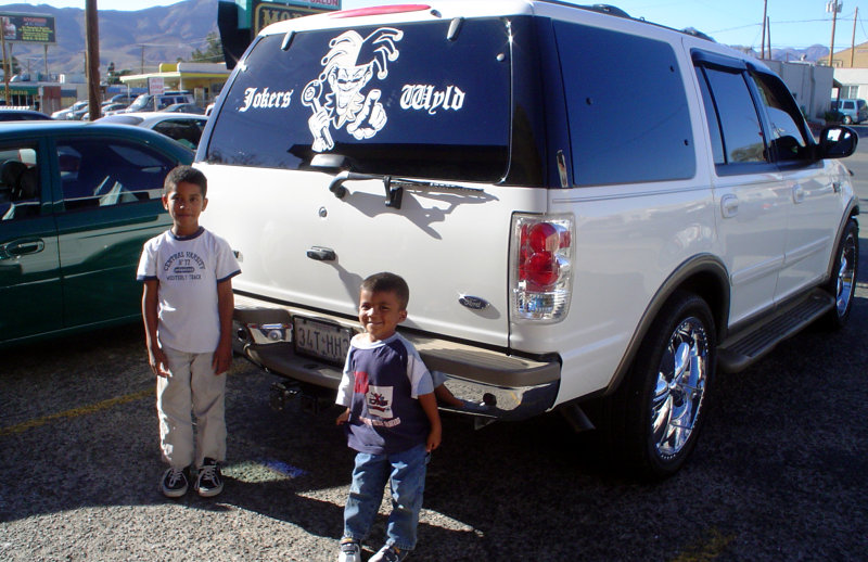 Kids posing next to Ford Expedition with custom car-club decal