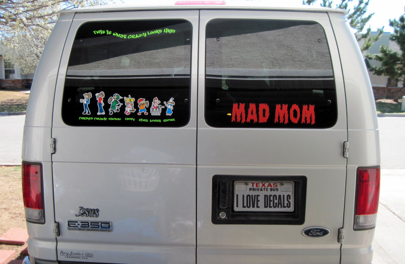 Mad Mom decal in read, and a family sticker, on the back of this Ford van.