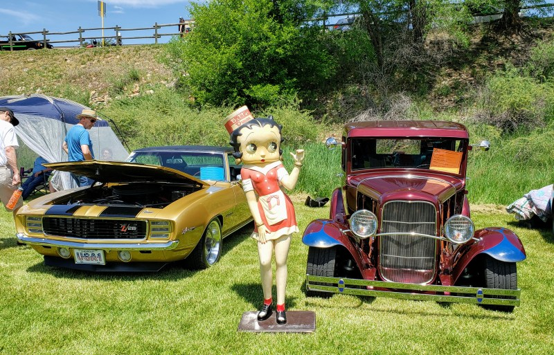 Betty Boop statue posing between fast cars