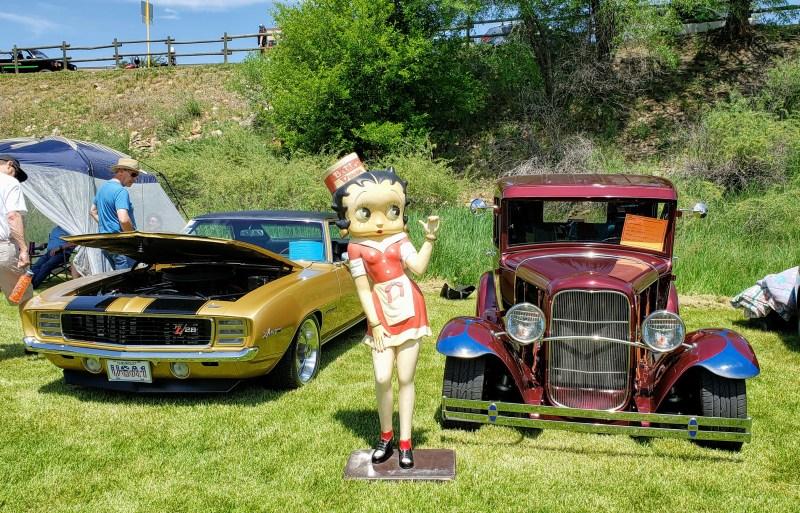 Betty Boop statue posing between fast cars