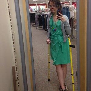 Image is of me at Target, taking a selfie in the mirror. I am using yellow forearm crutches. I am wearing a teal dress with a grey sweater, and a rainbow chunky necklace. Not looking sick despite, well, being sick.