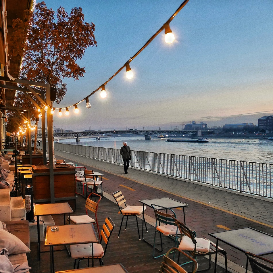 A lone stroller passes a riverside cafe at sunset on the Danube River in December.