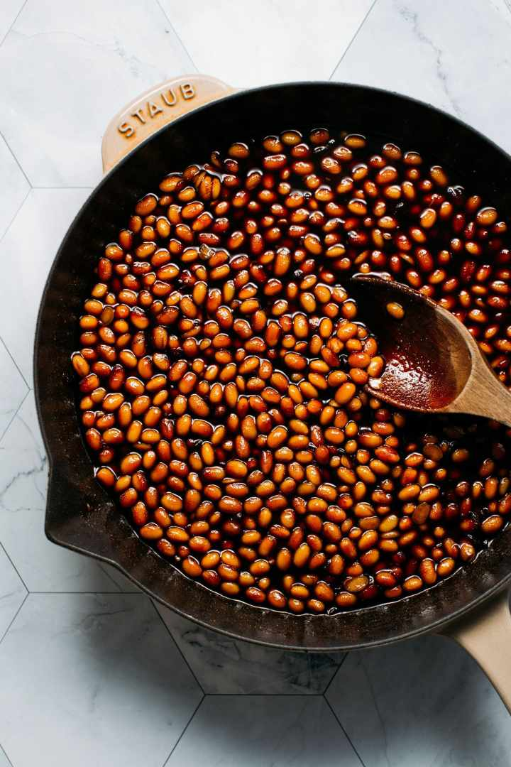 Whole soybeans in a skillet with soy sauce and sugar.