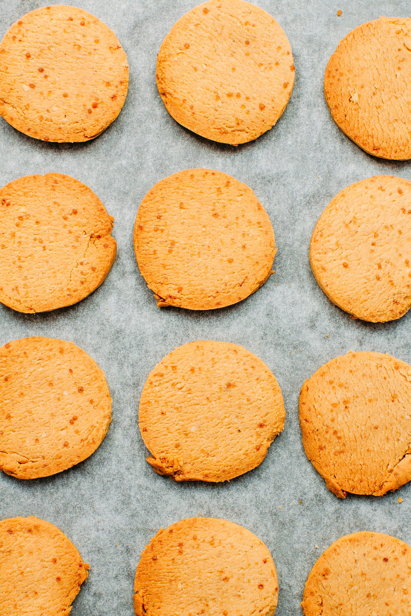 Vegan shortbread cookies on a baking sheet with parchment paper.