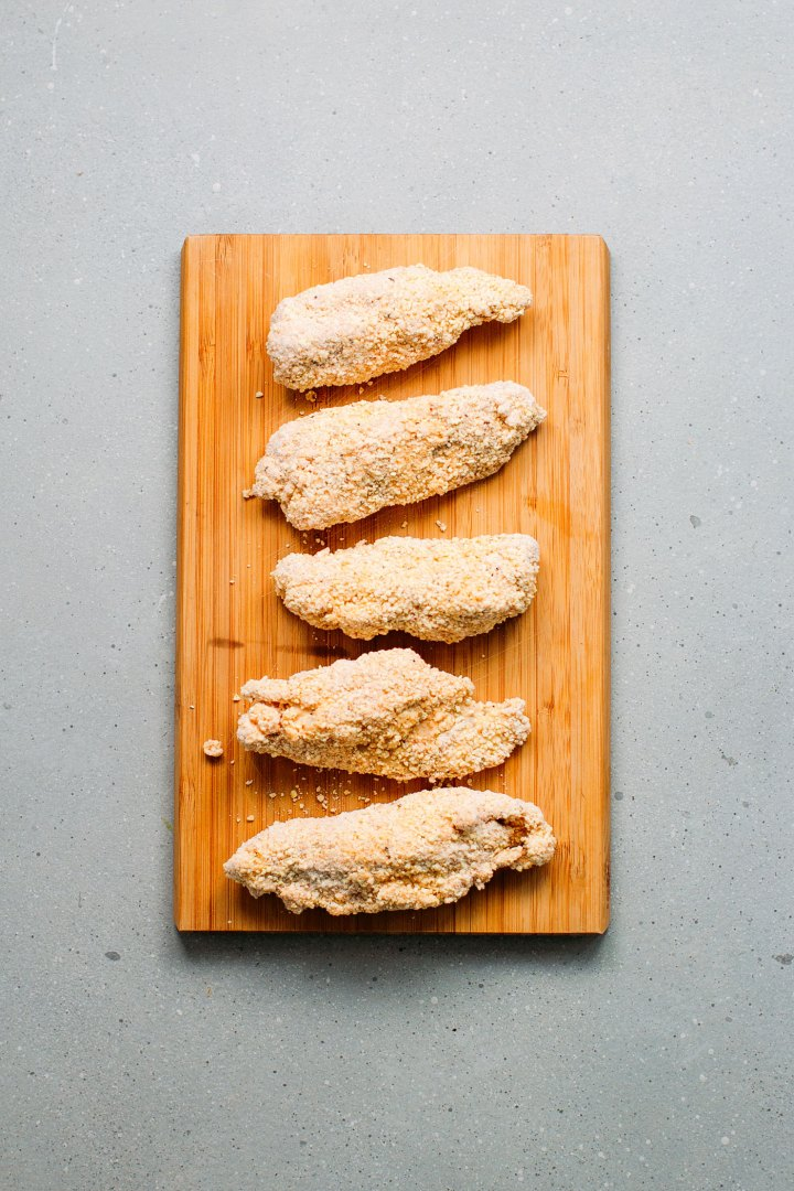 Vegan chicken nuggets before frying on a wooden board.