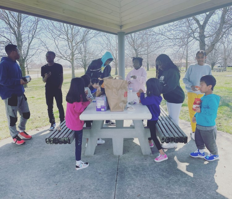 A family gathered around a picnic table under a shelter at a highway rest stop. The family is eating lunch of sandwiches and potato chips.