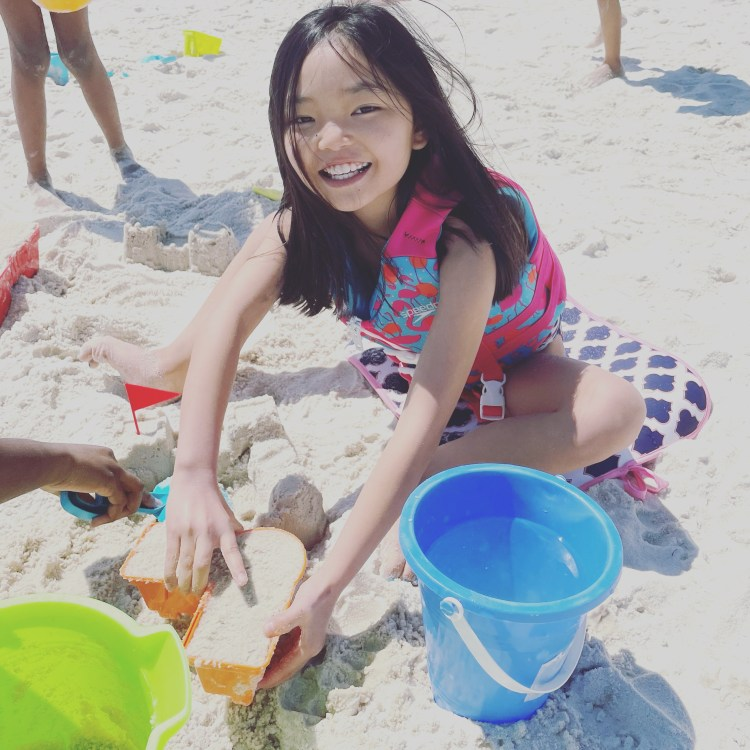 Tess, a small Asian girl, sitting on the beach playing with sand toys. She is sitting on a colorful mat in the sand. She is wearing a brightly colored life vest and swim suit.