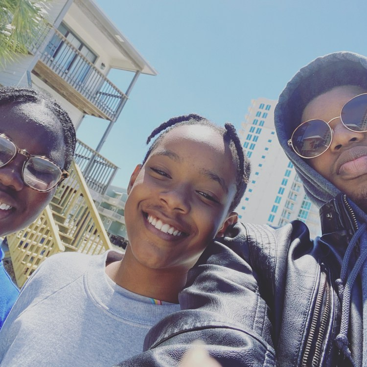 A selfie of three children, all Black. They are smiling into the camera as they stand close together.